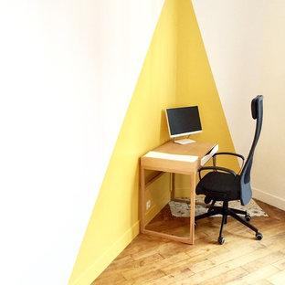 Foto di un ufficio nordico con pareti gialle, parquet chiaro, scrivania autoportante e pavimento marrone