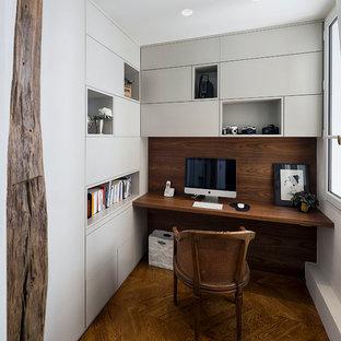 Exemple d'un grand bureau tendance avec un sol en bois foncé, aucune cheminée, un bureau intégré, un sol marron et un mur blanc.