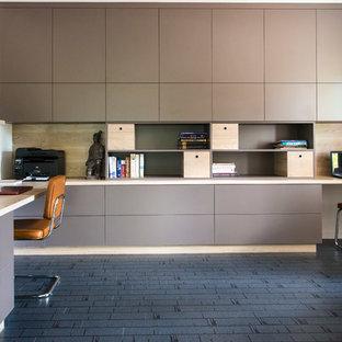 Immagine di un ufficio minimal di medie dimensioni con pareti bianche, pavimento in laminato, scrivania incassata e pavimento grigio