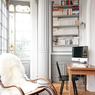 Aménagement d'un bureau contemporain de taille moyenne avec un mur blanc, un sol en bois brun et un bureau indépendant.