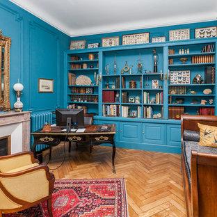 トゥールーズの広いヴィクトリアン調のおしゃれなホームオフィス・書斎 (ライブラリー、青い壁、淡色無垢フローリング、標準型暖炉、石材の暖炉まわり、自立型机) の写真