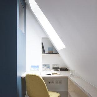 Bild på ett litet funkis hemmabibliotek, med vita väggar, ett inbyggt skrivbord, brunt golv och klinkergolv i terrakotta