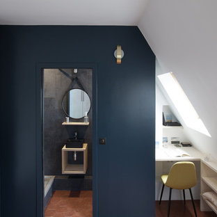 Small contemporary study in Paris with blue walls, terracotta flooring, a built-in desk and brown floors.