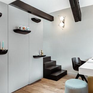 Aménagement d'un bureau scandinave avec un mur gris, un sol en bois clair, aucune cheminée et un bureau indépendant.