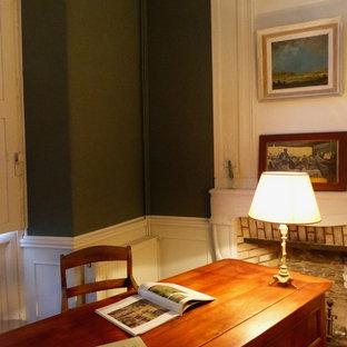 Immagine di uno studio moderno di medie dimensioni con pareti blu, pavimento in legno massello medio, camino classico, cornice del camino in pietra e pavimento marrone