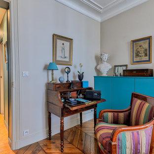 Idée de décoration pour un petit bureau design avec aucune cheminée, un bureau indépendant, un mur beige et un sol en bois brun.
