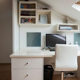 Cette image montre un petit bureau design avec un mur blanc, un sol en bois clair et un bureau intégré.