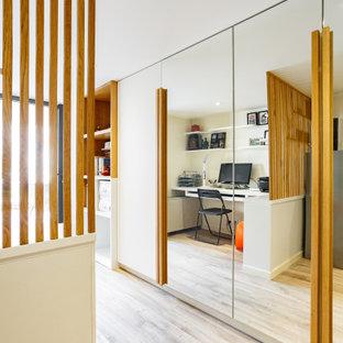 На фото: маленькое рабочее место в современном стиле с белыми стенами, полом из линолеума, встроенным рабочим столом и коричневым полом с