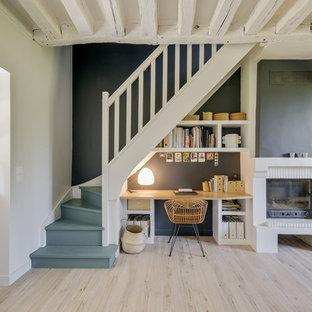 Inspiration för ett mellanstort medelhavsstil hemmabibliotek, med svarta väggar, laminatgolv, en standard öppen spis, en spiselkrans i tegelsten, ett inbyggt skrivbord och beiget golv