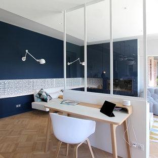Réalisation d'un bureau design avec un mur bleu, un sol en bois clair, un bureau indépendant et une cheminée standard.