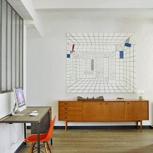 Cette photo montre un bureau éclectique de taille moyenne avec un mur blanc, un sol en bois brun et un bureau indépendant.