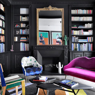 Medium sized bohemian home office in London with a reading nook, black walls, a standard fireplace, a metal fireplace surround and grey floors.