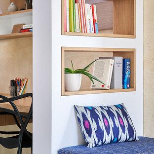 Foto di uno studio boho chic di medie dimensioni con libreria, pareti beige, pavimento in cemento, scrivania incassata e pavimento grigio