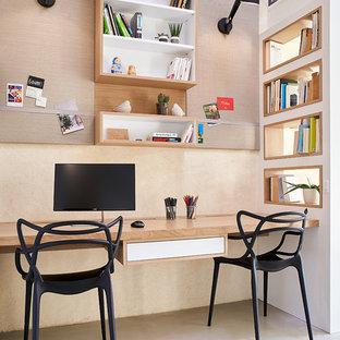 ナントの中サイズのエクレクティックスタイルのおしゃれなホームオフィス・仕事部屋 (ライブラリー、ベージュの壁、コンクリートの床、造り付け机、グレーの床) の写真