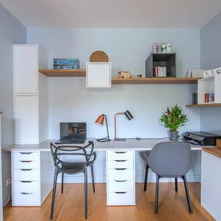 Exemple d'un grand bureau tendance avec un mur gris et un bureau intégré.