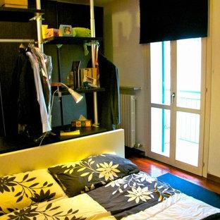 Modelo de dormitorio principal, contemporáneo, de tamaño medio, con paredes púrpuras y suelo de madera oscura