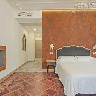 Ispirazione per una camera matrimoniale classica con pareti bianche, camino classico e pavimento marrone