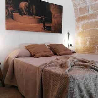 Modelo de dormitorio principal, rústico, de tamaño medio, con paredes blancas, suelo de piedra caliza y suelo beige