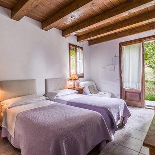 Immagine di una camera degli ospiti country di medie dimensioni con pareti bianche e pavimento grigio