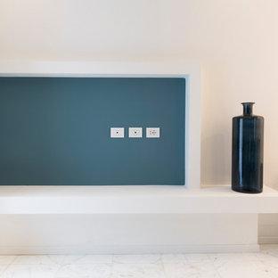 Imagen de dormitorio tipo loft, actual, pequeño, con paredes azules, suelo de mármol y suelo blanco