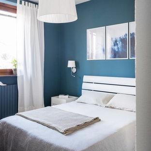 Foto di una piccola camera matrimoniale design con pareti blu, pavimento in gres porcellanato e pavimento marrone