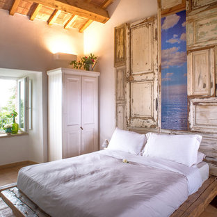 Photo of a mediterranean bedroom in Other with white walls, terra-cotta floors and brown floor.