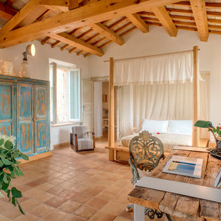 Imagen de dormitorio mediterráneo con paredes blancas, suelo de baldosas de terracota y suelo marrón