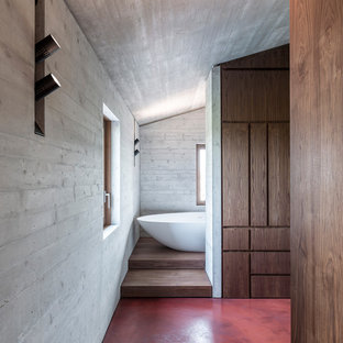 Photo of a contemporary master bedroom in Other with concrete flooring and red floors.