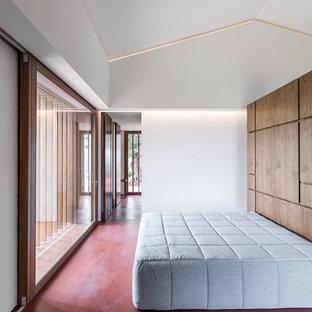 Foto de habitación de invitados actual, grande, con suelo de cemento y suelo rojo