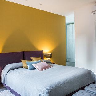 Immagine di una piccola camera matrimoniale design con pareti gialle e pavimento grigio
