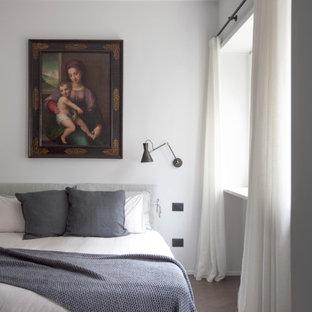 Immagine di una camera da letto design con pareti bianche, parquet scuro e pavimento marrone