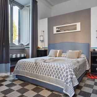Ispirazione per una camera matrimoniale design con pareti bianche e pavimento rosso