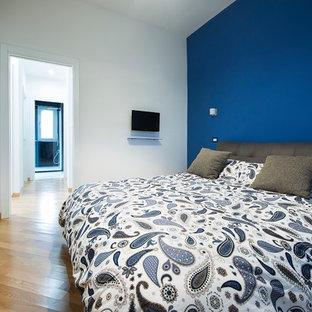 Immagine di una camera degli ospiti contemporanea con pareti blu, parquet chiaro e pavimento marrone