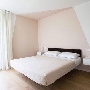 Immagine di una camera matrimoniale minimal con parquet chiaro, pareti multicolore e pavimento beige