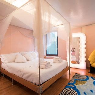 Esempio di una camera matrimoniale eclettica di medie dimensioni con pareti rosa, pavimento in legno massello medio e pavimento marrone