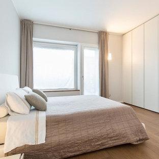 Esempio di una camera matrimoniale minimal con pareti bianche, pavimento in legno massello medio, nessun camino e pavimento marrone