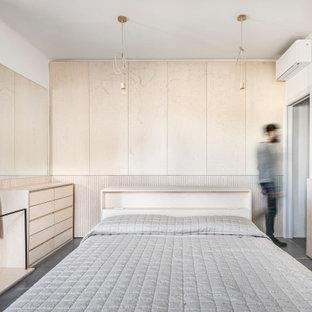 Foto di una camera matrimoniale design di medie dimensioni con pareti bianche, pavimento in cemento e pavimento grigio