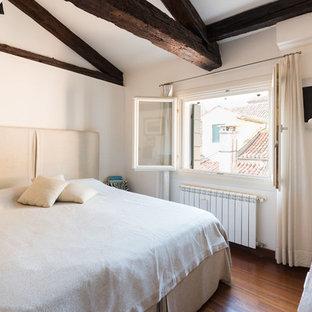 Esempio di una camera degli ospiti mediterranea con pareti bianche, pavimento in legno massello medio e pavimento marrone