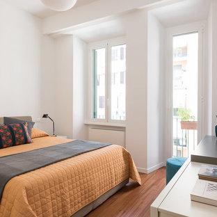 Esempio di una camera degli ospiti minimal con pareti bianche, pavimento in legno massello medio e pavimento marrone