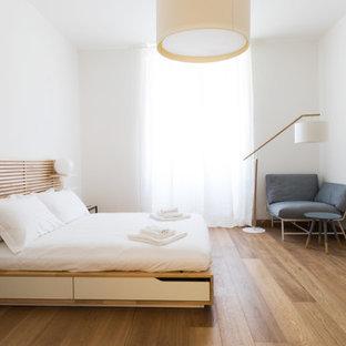 Esempio di una camera da letto contemporanea con pareti bianche, pavimento in legno massello medio e pavimento marrone