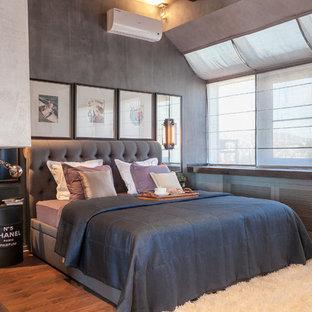 Foto di una camera degli ospiti industriale con pareti grigie, pavimento in legno massello medio e pavimento marrone