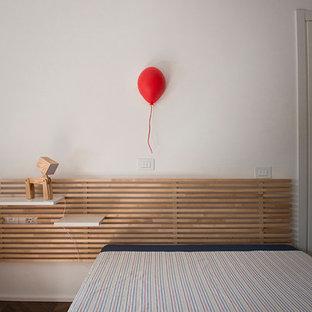 Imagen de dormitorio contemporáneo, de tamaño medio, con paredes blancas, suelo de madera en tonos medios, chimeneas suspendidas, marco de chimenea de yeso y suelo marrón
