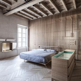 Immagine di una grande camera matrimoniale design con pareti grigie, parquet chiaro, camino sospeso e cornice del camino in pietra