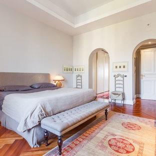 Immagine di una grande camera padronale eclettica con pareti grigie e pavimento in legno massello medio