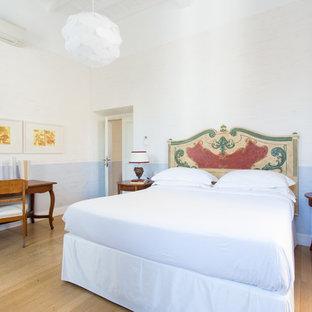 Ispirazione per una camera da letto mediterranea con pareti blu, parquet chiaro e pavimento beige