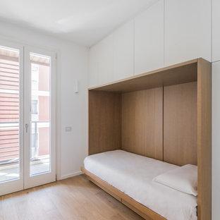Ispirazione per una camera da letto moderna con pareti bianche e parquet chiaro
