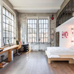 Large industrial master bedroom in Milan with dark hardwood floors, brown floor and grey walls.