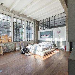 Esempio di una camera da letto industriale con pareti grigie, pavimento in legno massello medio e pavimento marrone