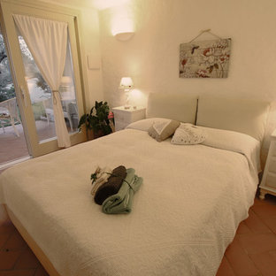 Small modern guest bedroom in Other with beige walls and terra-cotta floors.