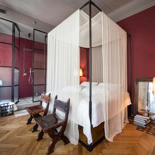 Esempio di una camera matrimoniale tradizionale di medie dimensioni con pareti rosse, pavimento in legno massello medio, nessun camino e pavimento marrone